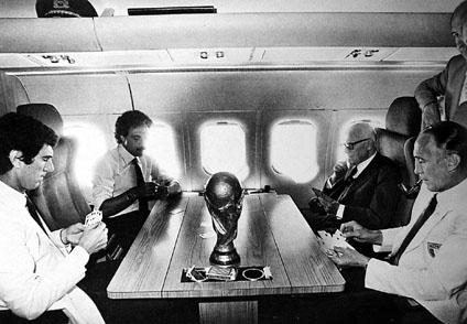 Il Presidente della Repubblica Sandro Pertini con Zoff, Causio e Bearzot sul DC9 militare che li sta riportando da Madrid a Roma. Sul tavolo la coppa del Mundial, 12 luglio 1982.