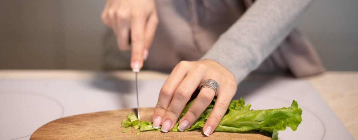 crop housewife cutting fresh salad in kitchen