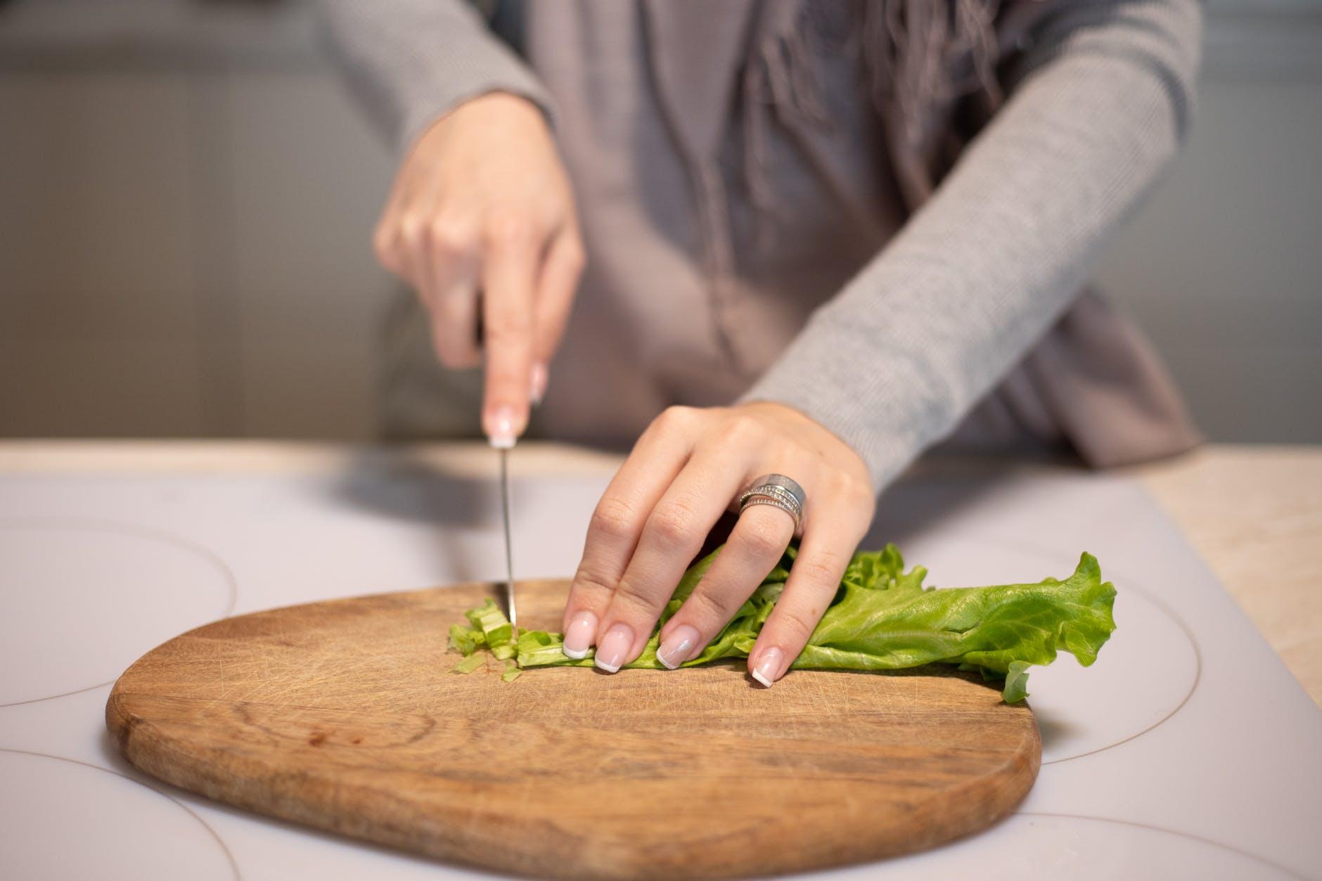 crop housewife cutting fresh salad in kitchen