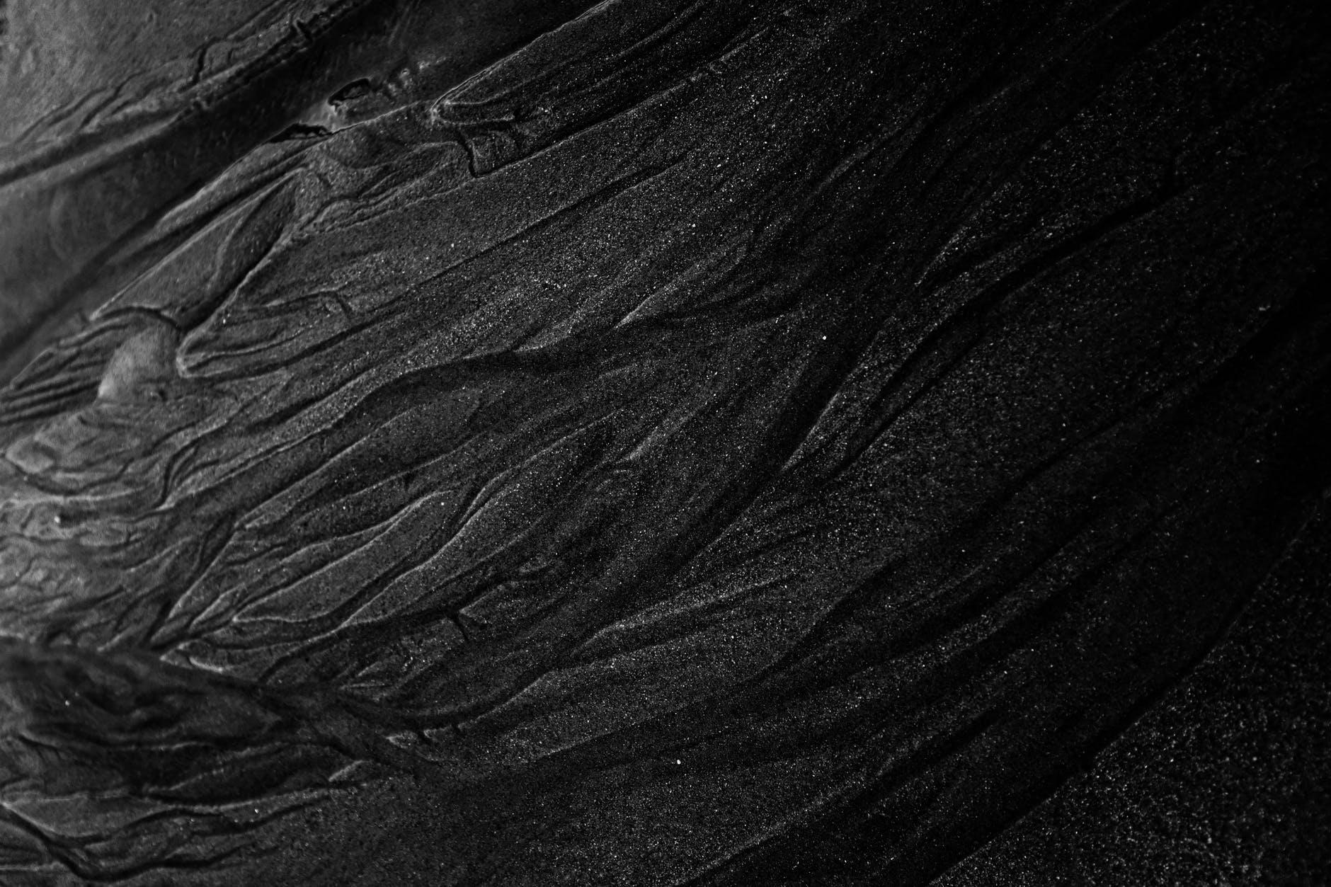 rough dark sand of shallow river